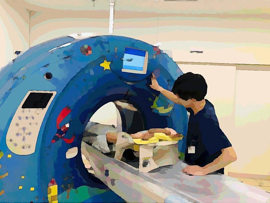 こちらはCT装置です。CTはリング状の機械の中で、X線を照射し体の輪切りの写真を撮影する検査を行います。撮影された細かい輪切りの画像を使い、いろいろな角度からの画像や3Dの画像を作ることが可能です。画像では腹部撮影を行うため、検査説明を行いながら位置合わせをしています。
